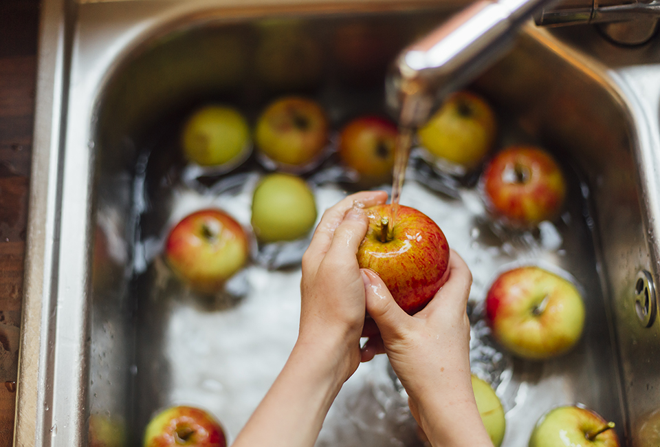 Hands washing apples